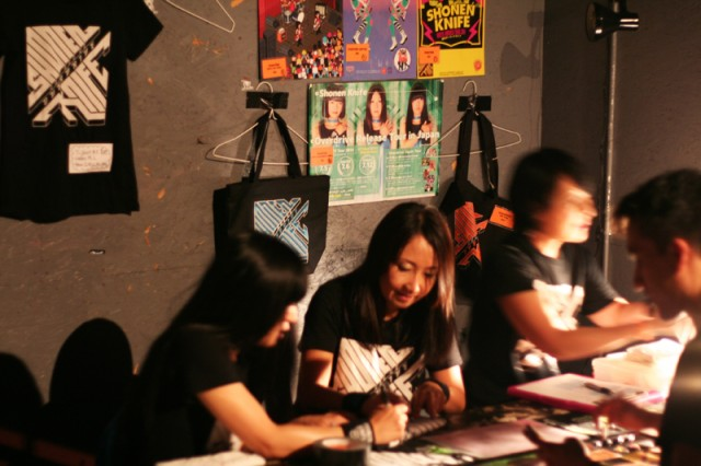 Shonen Knife autographs merch after the show.